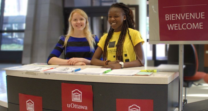 Two girls at the uOttawa Aiport Welcome stand | Deux femmes au kiosque d'accueil de l'université d'Ottawa à l'aéroport