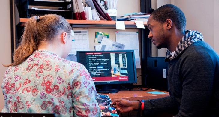 Deux étudiants qui se parlent et regardent un document