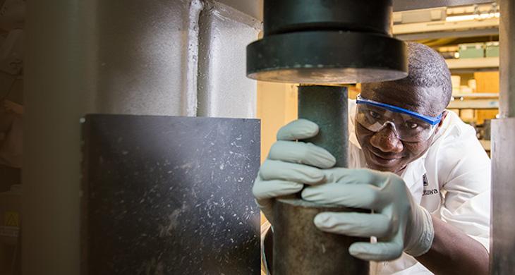 Moussa Thiam puts a cement sample into a compression machine