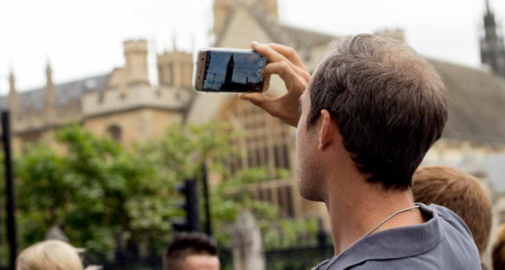 Student taking a photo with his cellphone in Westminster, UK