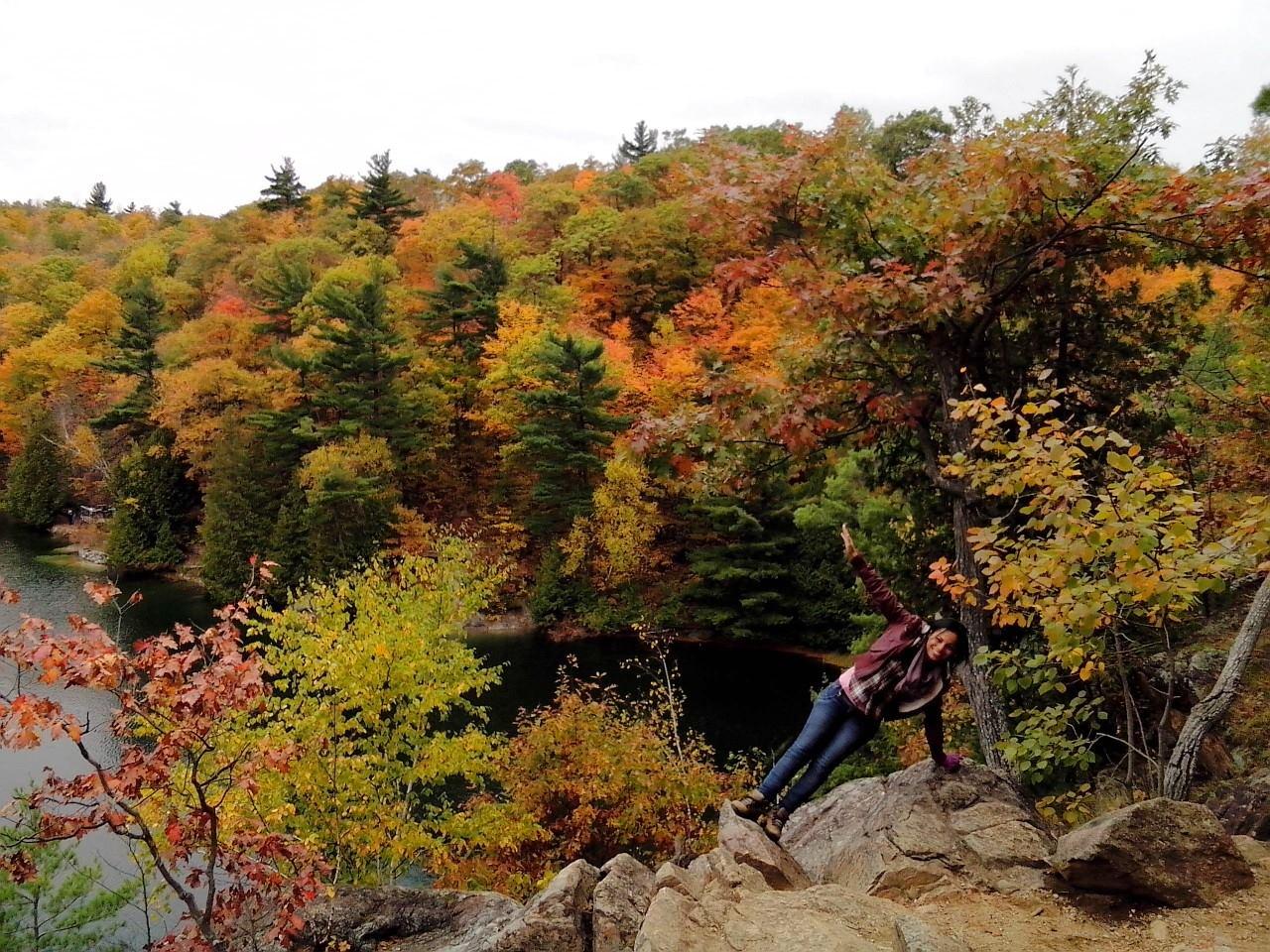 Étudiante parrainée qui se tient en équilibre sur sa main gauche devant un lac et des arbres