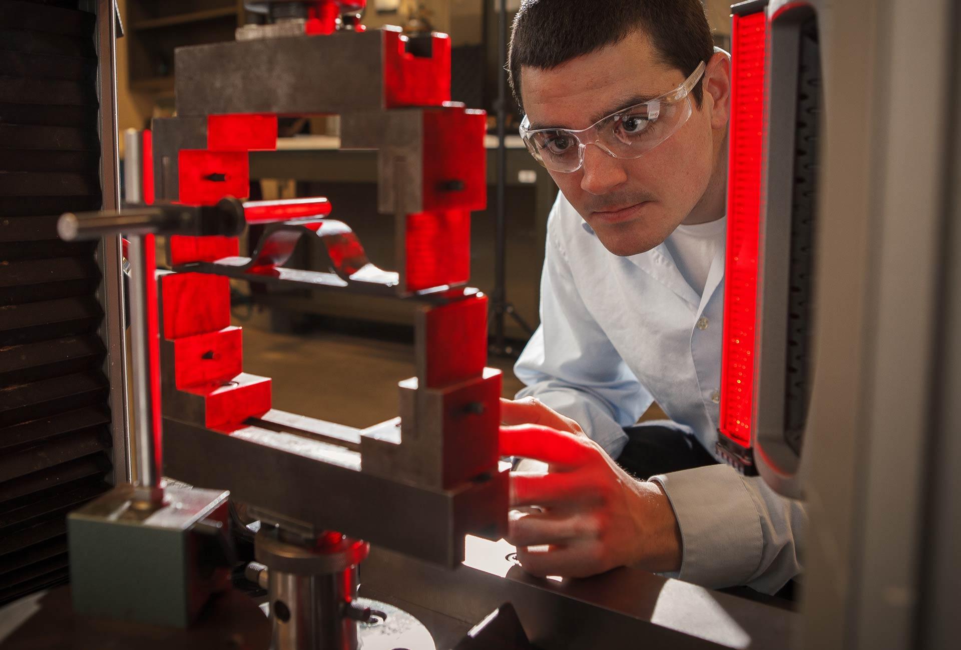 Un étudiant de la Faculté de génie portant un uniforme de laboratoire et des lunettes protectrices manipule des instruments lors d'une expérience scientifique.