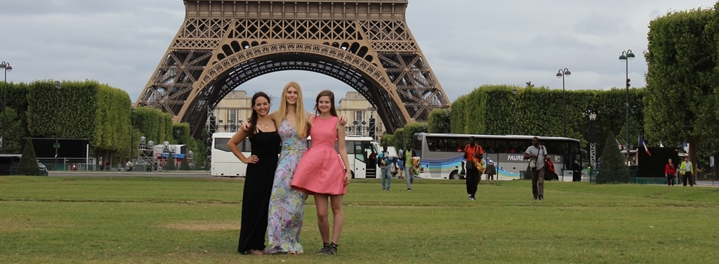 Three women, including Chelsea Cooligan in front of the Eiffel Tower.