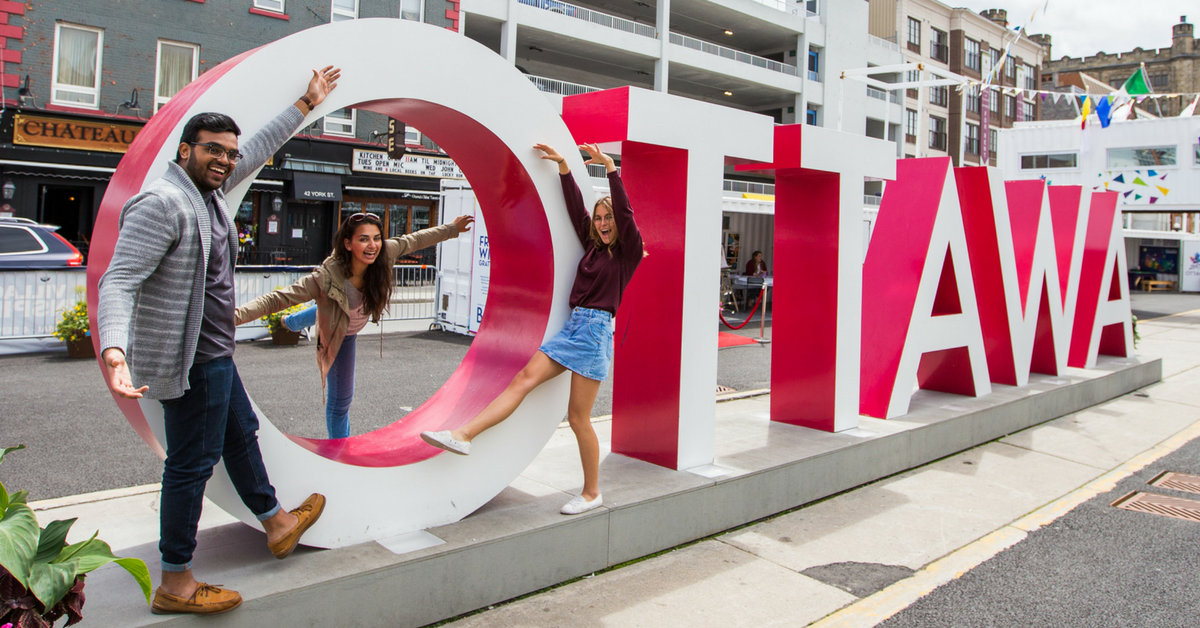 three person standing in front of the Ottawa sign in ByWard Market